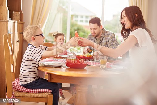 a young family sit at the table and make mealtime fun