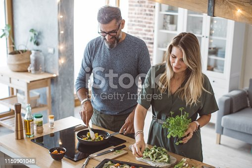 Man and woman preparing delicious vegetable meal, everything is so green, healthy and freshly harvested from garden