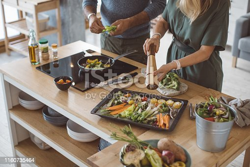 Couple preparing delicious vegetable meal, everything is so green, healthy and freshly harvested from garden