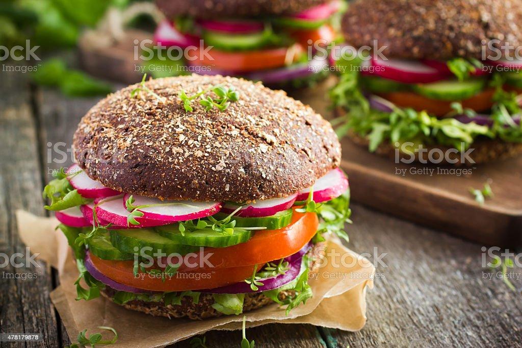 Healthy fast food. Vegan rye burger with fresh vegetables stock photo