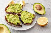 Healthy fat diet, nutritious snack and mexican food conceptual idea with smashed avocado into guacamole spread on rye bread toast surrounded by lemon and avocados isolated on white wood table