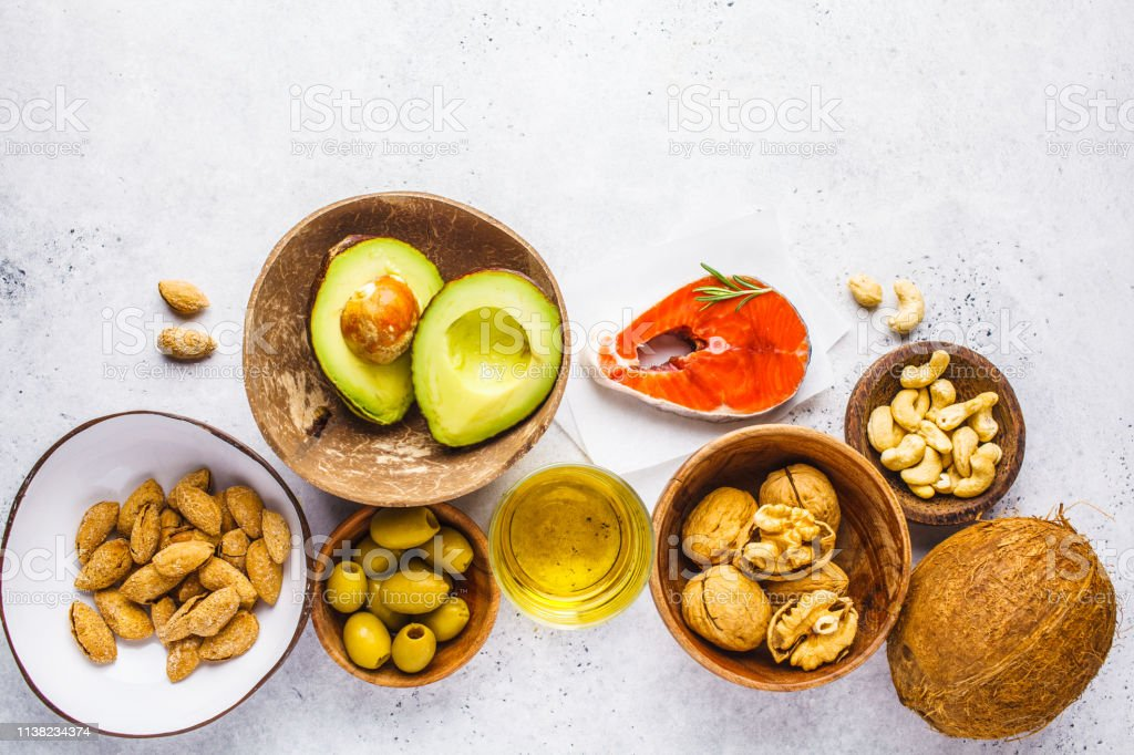 fish, nuts, oil, olives, avocado on white background, copy space