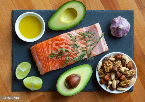 Table top still life of foods high in healthy fats such as olive oil, Salmon, nuts and avocados with vegetables and herbs.