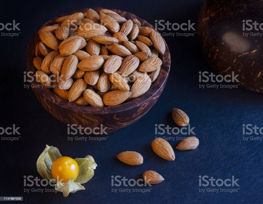 healthy fats illustrated with almonds in a wooden bowl on slate plate...