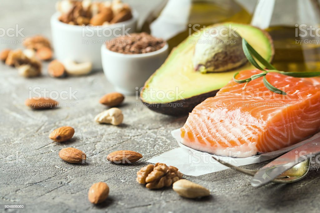 Healthy fats in nutrition - salmon, avocado, oil, nuts. Concept of...