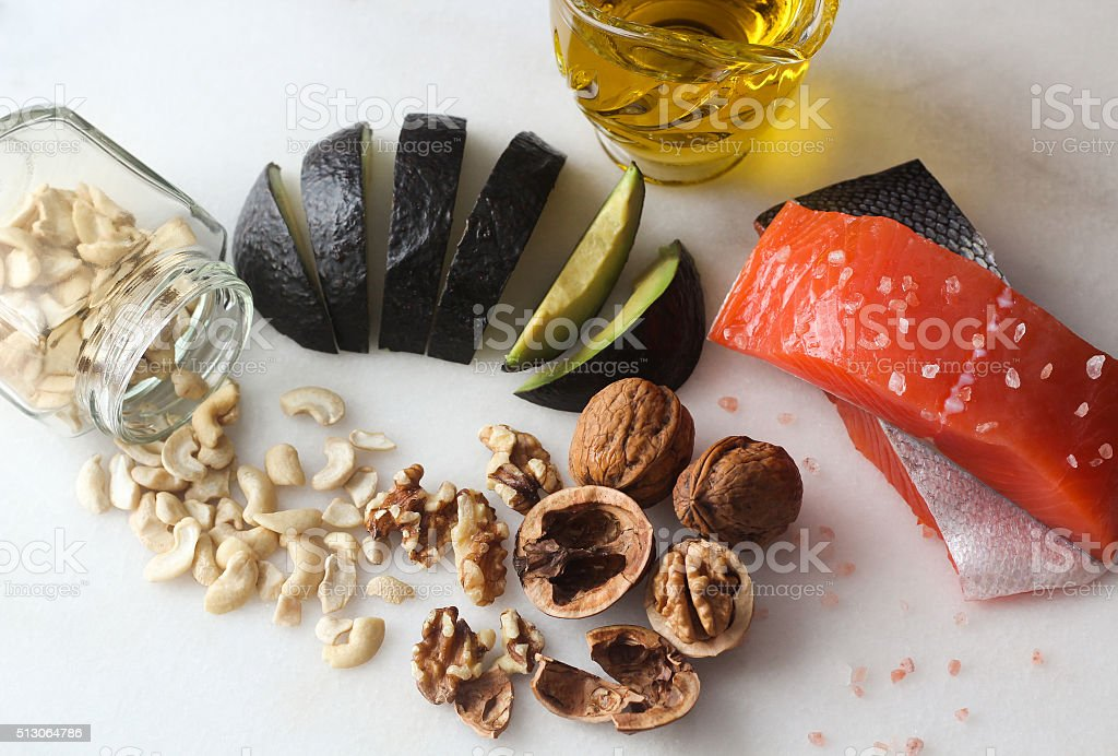 Salmon, olive oil, avocado, walnuts, cashews, rock salt overhead shot...