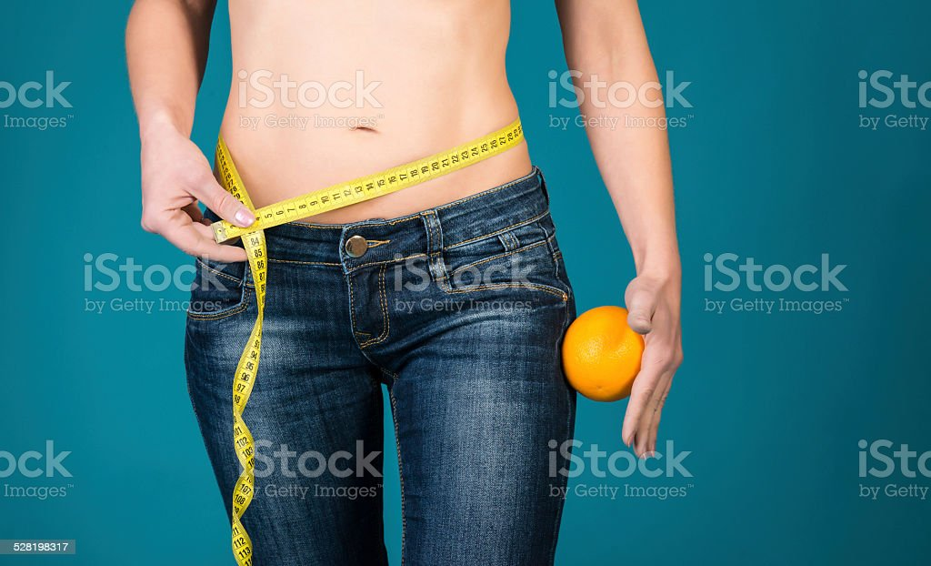 Healthy female body with orange and measuring tape. stock photo