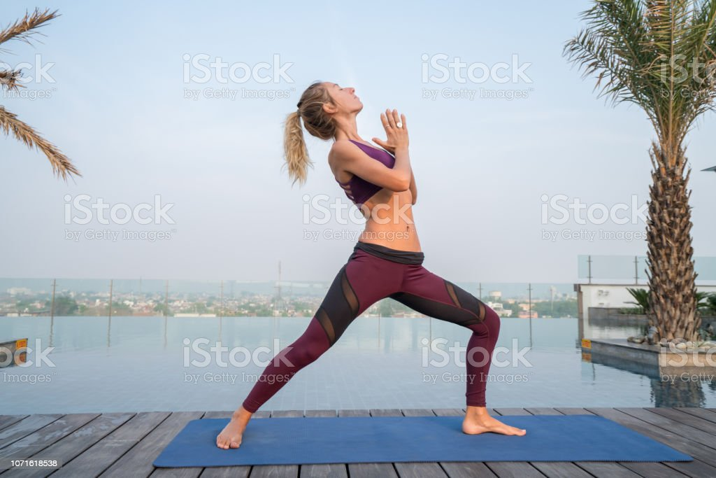 Young woman by an infinity pool exercising yoga on yoga mat in Agra,...