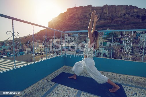 Young woman on rooftop exercising yoga on yoga mat in Jodhpur, India