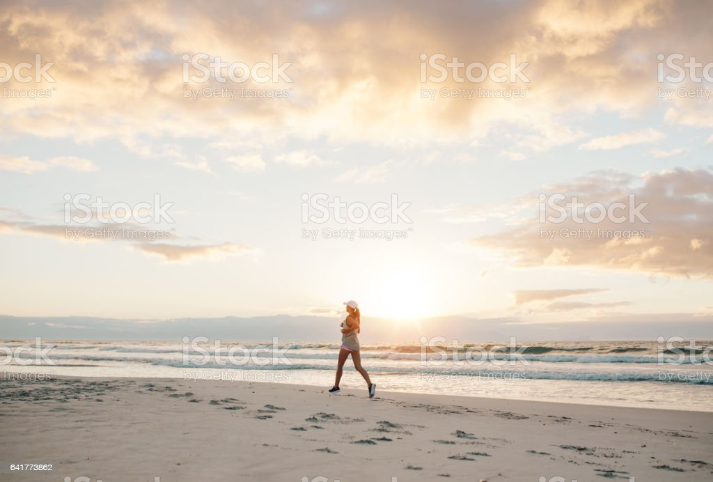 Healthy female jogging on the sea shore stock photo