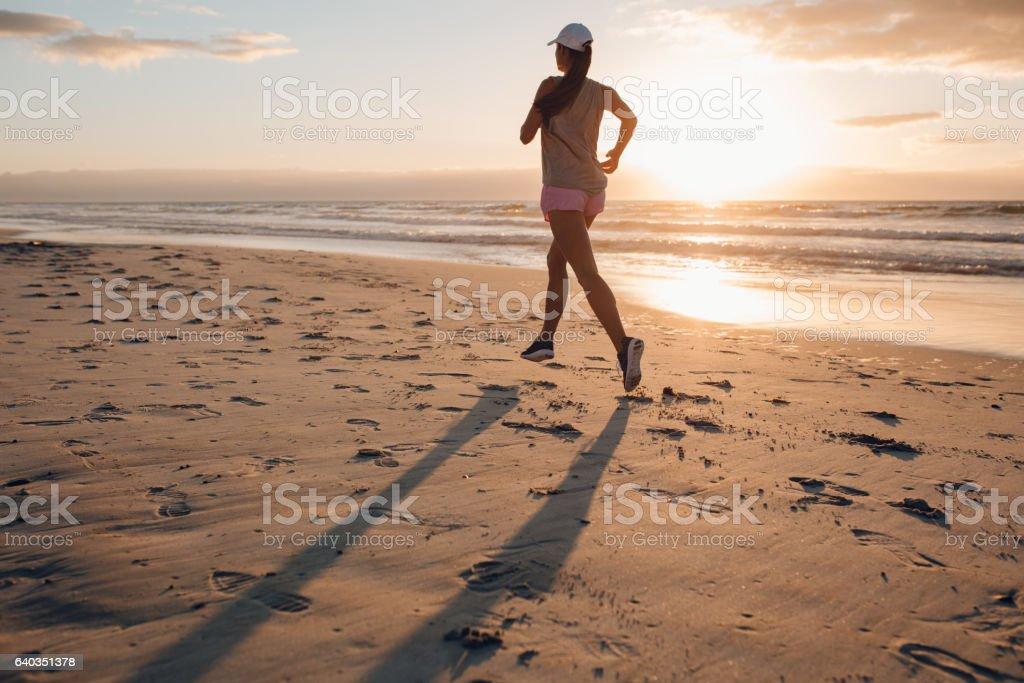 Healthy female running along the beach stock photo