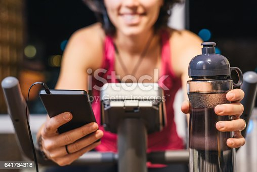 istock Healthy fit smiling woman training at home on exercise bike 641734318