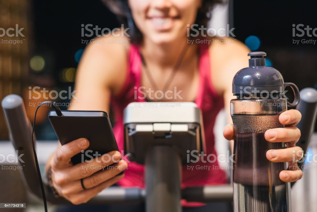 Healthy fit smiling woman training at home on exercise bike stock photo
