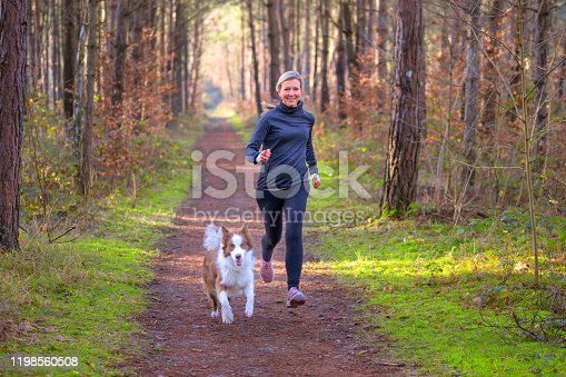 Healthy fit woman running with her dog jogging together through a forest along a footpath approaching the camera with a happy smile