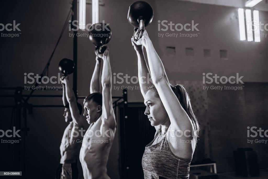 Healthy fit young athletes doing exercises with kettlebells at gym, men and women during weight lifting workout stock photo