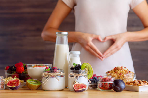 Healthy fitness food for breakfast Female make shape of heart with her hands. Light summer breakfast with organic yogurts, fruits, berries and nuts. Nutrition that promotes good digestion and functioning of gastrointestinal tract. bifidobacterium stock pictures, royalty-free photos & images