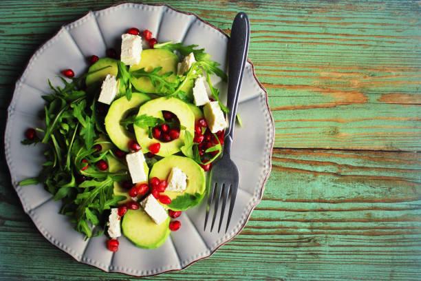 Healthy fitness salad with arugula, avocado, feta . Vegetarian nutritious salad. Keto diet. Keto lunch idea recipe stock photo