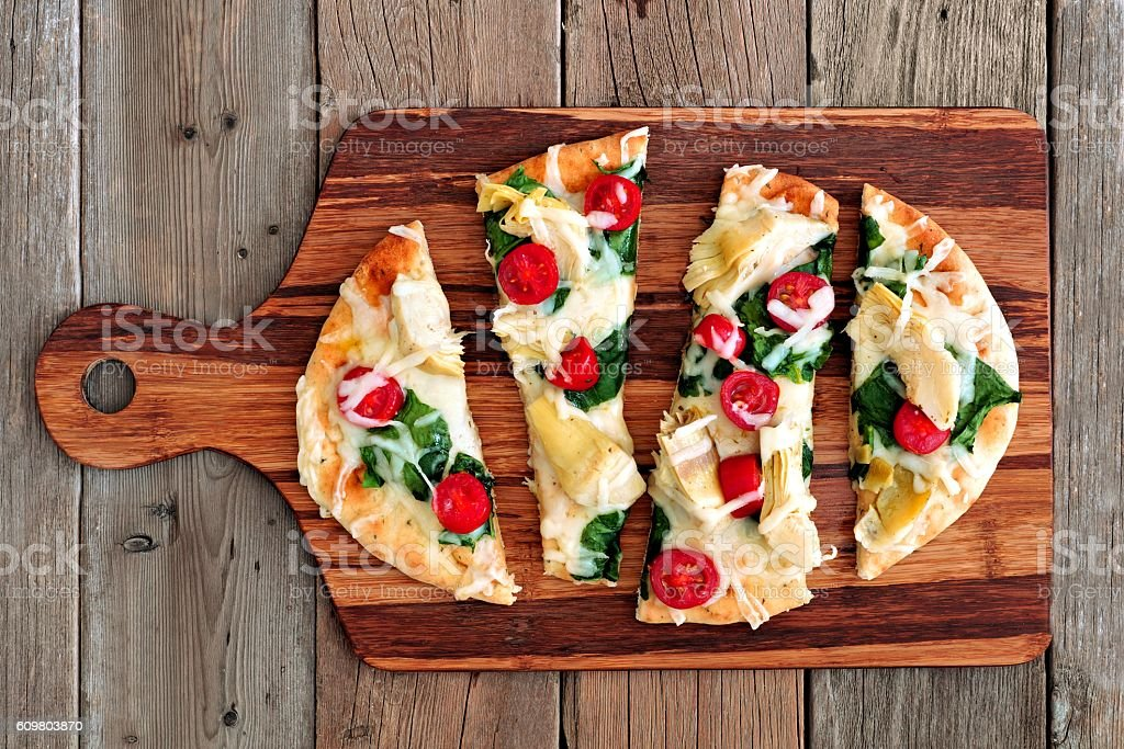 Healthy flatbread pizza on wooden paddle board stock photo