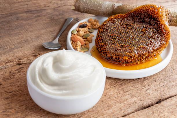 그라놀라와 벌꿀 빗을 나무 배경에 세라믹 그릇에 넣은 건강한 맛의 요구르트. 음식과 건강한 개념. 스톡 사진