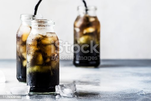 Healthy food and drink concept: cold black detox mineral water with crushed ice in glass bottles, with activated charcoal, gray stone table, trendy beverage, copy space, selective focus