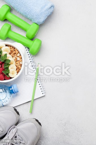Healthy food and fitness concept. Sport equipment and breakfast cereal. Top view flat lay with copy space for your text