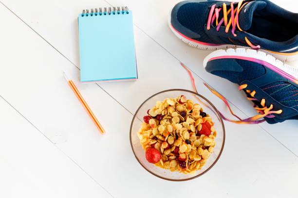 gesunde ernährung und gesunde lebensweise. abgeschrieben-buch mit einem leeren blatt für den text, müsli und ein sneaker auf einem weißen holzboden. ansicht von oben. textfreiraum - trainingstagebuch stock-fotos und bilder