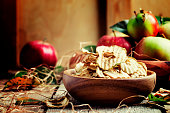 Healthy food: apple chips and fresh apples, decorations in the rustic style. Vintage wood background, selective focus