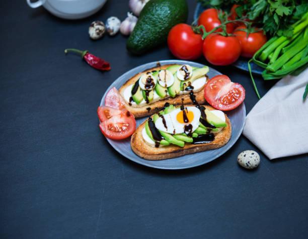 Gesunde seradienende Nahrung. Avocado Sandwich und Gemüse. Toast mit weißem Weichkäse, in Scheiben geschnittene Avocado, Wachtel fried und gekochte Eier gegossen Balsamico-Sauce für gesundes Frühstück oder Snack. – Foto