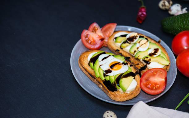 Gesunde seradienende Nahrung. Avocado Sandwich und Gemüse. Toast mit weißem Weichkäse, in Scheiben geschnittene Avocado, Wachtel gebraten und gekochte Eier gegossen Balsamico-Sauce für gesundes Frühstück oder Snack – Foto