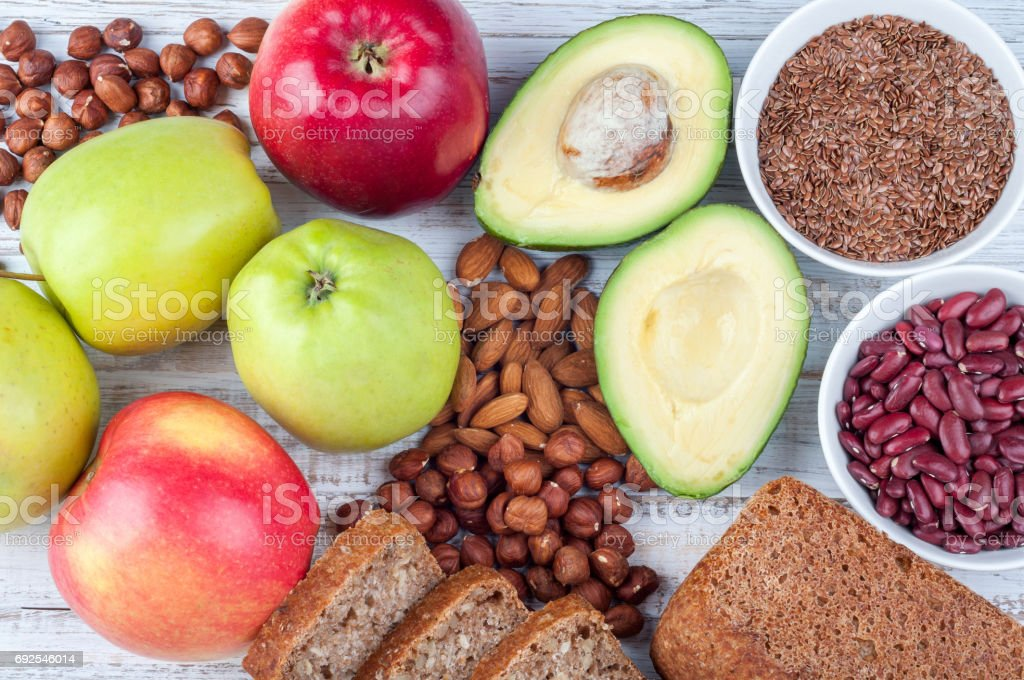 Healthy food - avokado, flax seeds, whole grain bread, nuts and apples on wooden background. Diet and healthy lifestyle concept. Vegetarian food stock photo