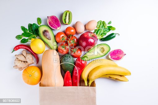 1126188273 istock photo Healthy food background. Healthy food in paper bag fruits and vegetables on white. Vegetarian food. Shopping food supermarket concept 937808502