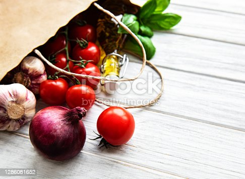 istock Healthy food background. Healthy  food in paper bag, vegetables on a white wooden background 1286081652