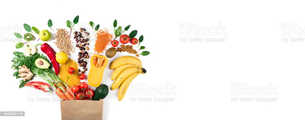 Healthy food background. Healthy vegetarian food in paper bag pasta, vegetables and fruits on white. Shopping food concept. Long format with copy space stock photo
