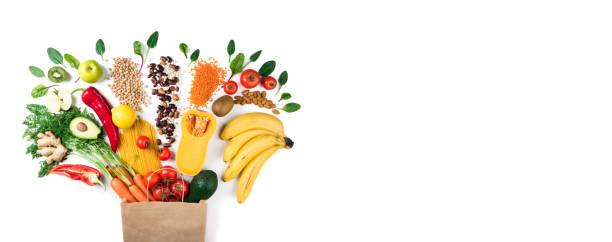 gesunde ernährung-hintergrund. gesunde vegetarische kost in papier tasche nudeln, gemüse und obst auf weiß. lebensmittel-shopping-konzept. langformat mit textfreiraum - kürbis kaufen stock-fotos und bilder