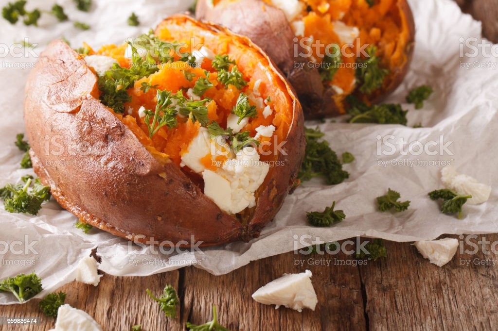 healthy food: baked sweet potato stuffed with cheese and parsley close-up. Horizontal stock photo