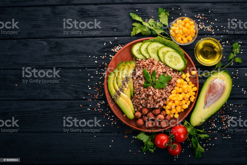 Healthy food. Buckwheat, avocado, cucumber, corn and hazelnut. On a wooden background. Top view. Free space for your text. stock photo