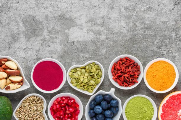 gezonde voeding schoon eten selectie: fruit, groenten, zaden, superfood, noten, bessen op grijze concrete achtergrond - spoorelement stockfoto's en -beelden