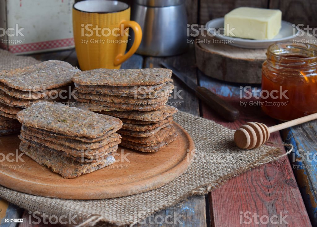 Healthy food concept. Breakfast with crispbreads, butter, jam, coffee. Flatbread crackers with sesame, flax seed, pumpkin and sunflower seeds. Diet crispy cookies. Snack gluten-free. Copy space stock photo