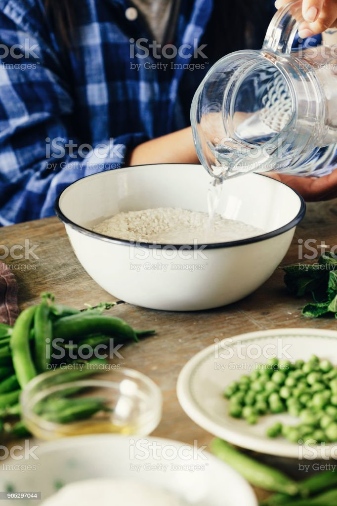 Healthy food concept. Raw ingredients for cooking risotto on wooden table. Woman cooking vegetarian risotto with green peas, mint and goat cheese royalty-free stock photo