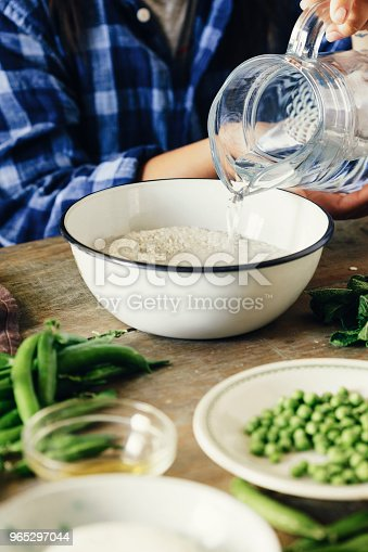 Healthy Food Concept Raw Ingredients For Cooking Risotto On Wooden Table Woman Cooking Vegetarian Risotto With Green Peas Mint And Goat Cheese Stock Photo & More Pictures of Adult