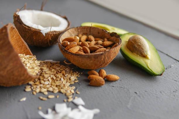 Conceito de comida saudável com abacate, cocos, amêndoas e aveia sobre fundo cinza perto da janela. - foto de acervo