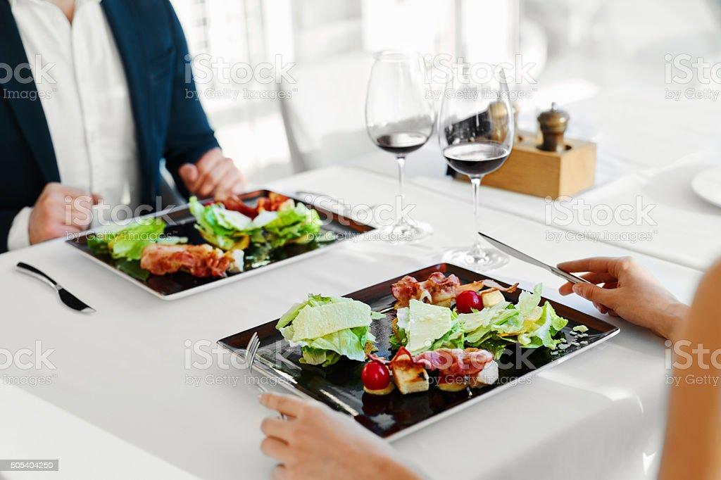 Gesunde Speisen. Paar Essen Caesar-Salat für Mahlzeit im Restaurant. – Foto