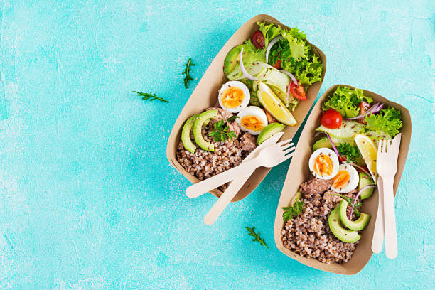 Healthy food delivery. Lunch- Buckwheat porridge, sliced tuna, boiled egg and fresh vegetable salad in zero waste containers  on blue background. Top view, flat lay stock photo