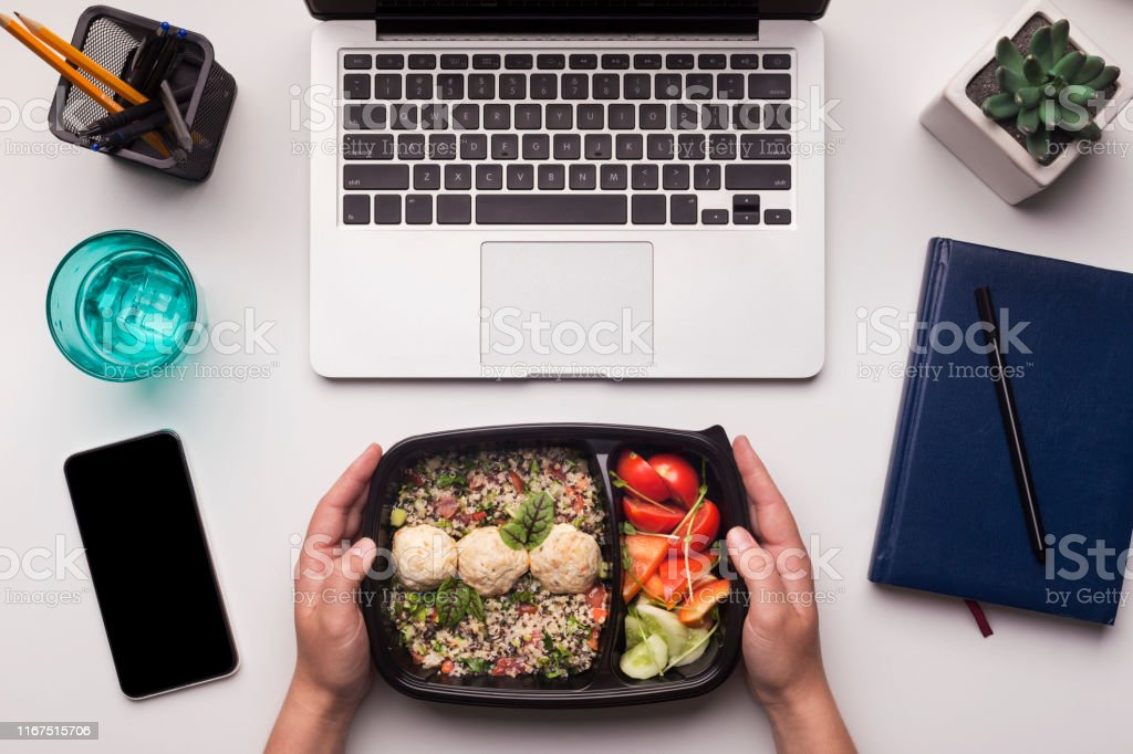 Healthy food delivery to work place in office, cellphone with blank...