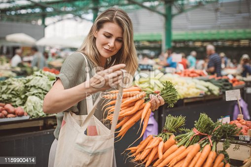 Cheerful woman selecting fresh vegetables in market, everything is fresh and organic