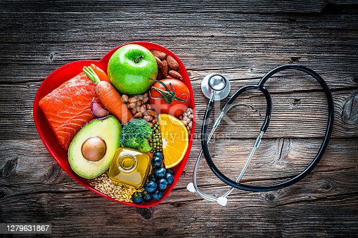 Healthy eating: fresh multicolored foods to help lower cholesterol levels and for heart care shot on wooden table. The composition includes oily fish like salmon. Beans like Pinto beans, soybeans and brown lentils. Vegetables like garlic, carrot, avocado, broccoli and tomato. Fruits like apple, orange and berries. Nuts like almonds. Olive oil. The food is arranged in a red heart shape tray and a stethoscope is beside it. High resolution 42Mp studio digital capture taken with SONY A7rII and Zeiss Batis 40mm F2.0 CF lens