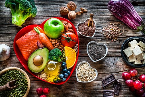 Healthy eating: group of fresh multicolored foods to help lower cholesterol levels and for heart care shot on wooden table. The composition includes oily fish like salmon. Beans like Pinto beans and brown lentils. Vegetables like garlic, avocado, broccoli, eggplant and tomatoes. Fruits like apple, grape, orange and berries. Nuts like almonds and walnuts. Soy products like tofu and soybeans. Cereals and seeds like chia seeds, flax seeds, oatmeal and barley. Olive oil, dark chocolate and yogurt with added sterols and stanols. High resolution 42Mp studio digital capture taken with SONY A7rII and Zeiss Batis 40mm F2.0 CF lens