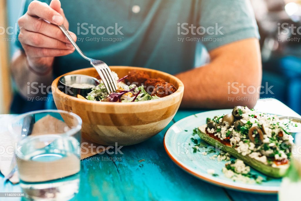 Healthy food for lunch Shot of a young man eating fresh vegan salad with chickpeas balls and sesame sauce on rustic wooden table Adult Stock Photo