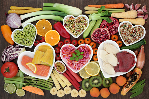Health food for weight loss concept with fish, meat, salads, fresh fruit and vegetables, herbs and herbal medicine used to help weight loss. Top view.