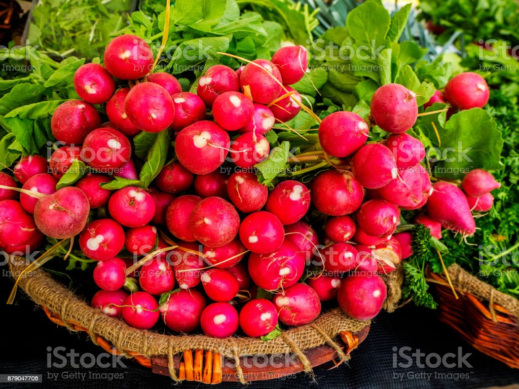 Healthy Food - Fresh, organic and locally grown Red Radishes, presented in round wicker baskets lined with hessian at Farmer's Market, Dubai. stock photo